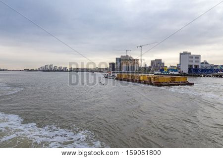 Tug pulling a full load of containers downriver on the River Thames in London