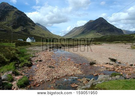 Cottage in Glencoe, Scotland, against the backdrop of Buachille Etive Beag