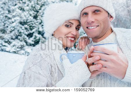 Couple in love with cups of hot tea in snow winter forest