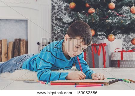 Writing letter to santa. Cute boy makes wish list of presents for christmas. Waiting for gift. Prepare for winter holidays