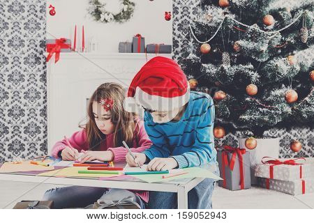 Writing letter to santa. Cute children in santa hat makes wish list of presents for christmas. Waiting for gift. Prepare for winter holidays. Boy and girl portrait