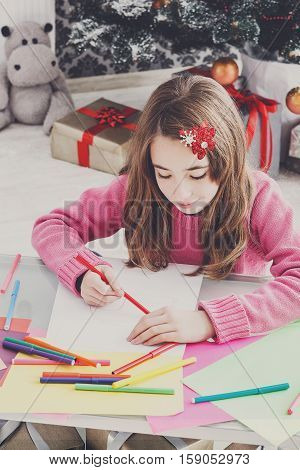 Writing letter to santa. Beautiful girl makes wish list of presents for christmas in decorated room. Waiting for gift. Prepare for winter holidays.
