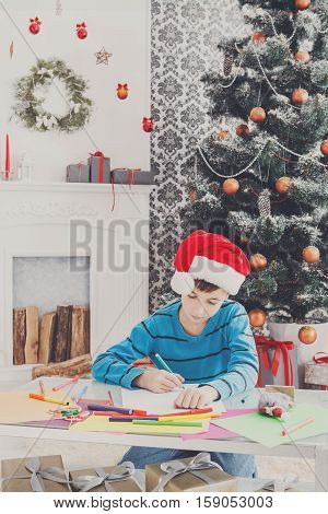 Writing letter to santa. Cute boy in santa hat makes wish list of presents for christmas. Waiting for gift. Prepare for winter holidays. Child portrait, vertical image