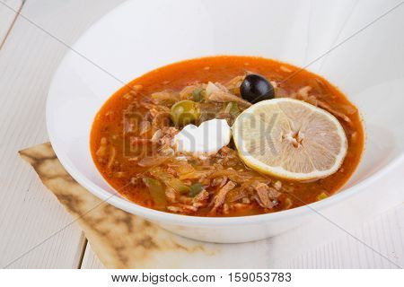 Russian solyanka soup in a white plate