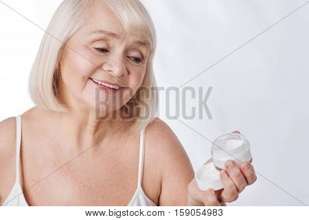 Anti age cosmetics. Delighted happy aged woman holding a bottle of moisture cream and smiling while fighting with age