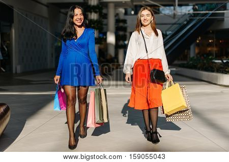 Two women walking in the mall after good shopping. Thay have fashion looks. They have many colorful shopping bags in their hands. Girls smiling. Sunny day