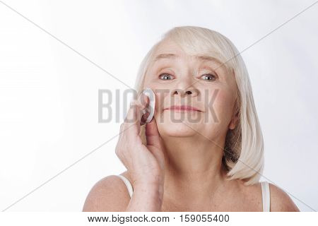 I care about my face. Pleasant optimistic senior woman holding a cotton pad and using it while having her daily skin care routine