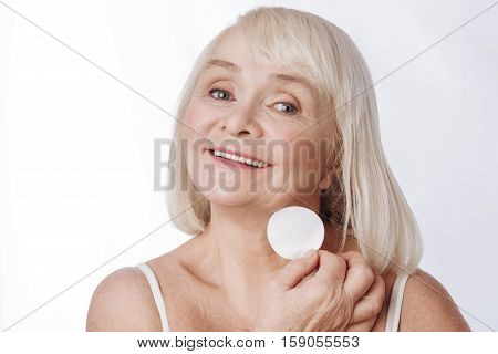 Skin care activities. Joyful pleasant senior woman holding a cotton pad and using it white cleaning her skin