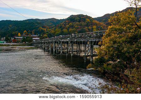 KYOTO, JAPAN - NOVEMBER 18, 2016 - Fall color attracts visitors to the Togetsu Bridge on the Katsura River in the Arashiyama area of Kyoto, Japan