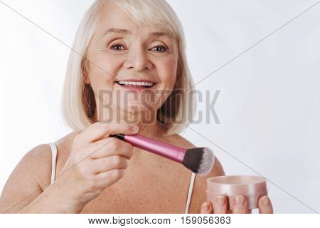 Reducing skin shine. Good looking happy retired woman holding a makeup brush and using it while applying face powder
