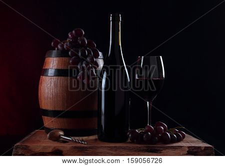 Barrel of vine bottle with red vine glass and fresh grapes
