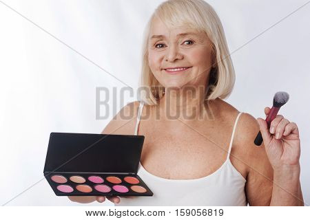 Professional cosmetics. Optimistic happy aged woman holding a cosmetic brush using rouge palette while putting on make up
