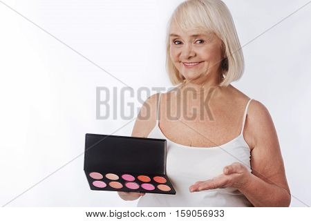Rouge palette. Happy nice elderly woman holding a rouge palette and pointing at it while using professional decorative cosmetics