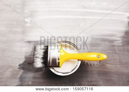 Paintbrush and a opened can of white paint on fresh painted wooden surface