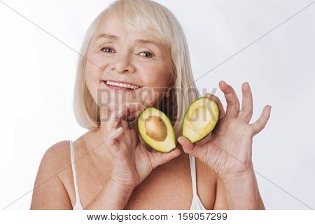 Useful fruit. Cheerful happy elderly woman standing against the white background and holding avocado halves while using fruits for cosmetic purposes