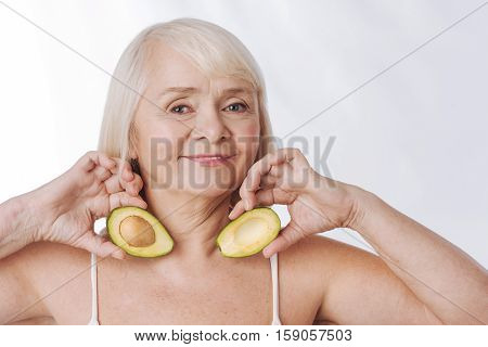 I love fruits. Optimistic nice aged woman holding avocado halves and putting them to her neck while using them for beauty purposes