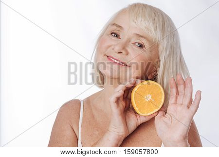 Delighted look. Positive joyful aged woman smiling and inclining her head while holding an orange half