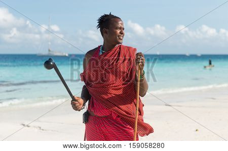 ZANZIBAR, TANZANIYA- JULY 17: tsmiling masai with sunglasses on a beach and blue sea on the background on July 17, 2016 in Zanzibar