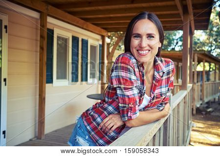Close-up side shot of a toothy smile of relaxed woman who is leaning on the handrail near the wooden rest house. Spending summer vocation. Having a rest