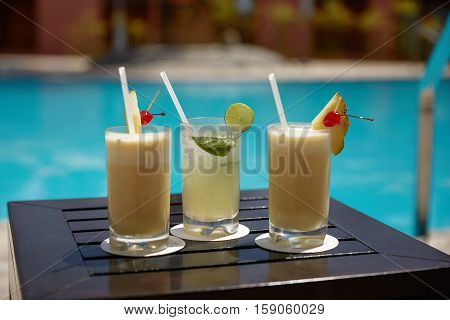 Cocktails of Mojito and Pina Colada on Wooden Table Near the Swimming Pool During Summer.
