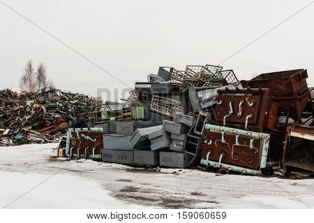 Two big scrap metal heap on snow in winter.