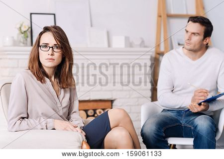Troubled mood. Distressed tired woman sitting in the arm chair and sitting in the arm chair while discussing her problems with professional psychologist