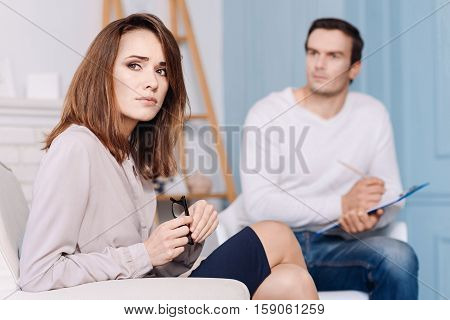 Reveal your thoughts. Pleasant distressed woman thinking and sitting in the arm chair while discussing her problems with professional psychologist