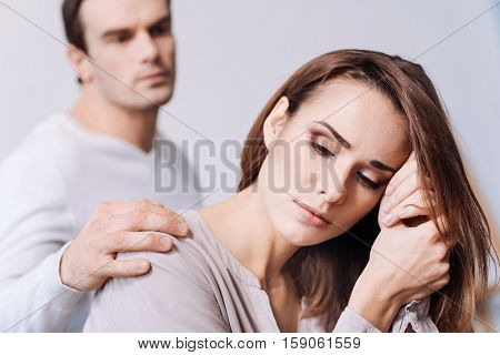 Can I help you.Tired distressed woman feeling sad and sitting at home while her husband comforting her