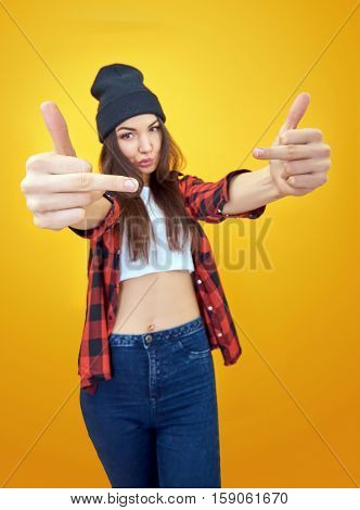 Hipster girl in jeans, checked shirt and hat showing middle fingers over yellow background. Impertinent behaviour. Hipsters. Provocation. Aggression. Naughtiness.