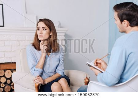 Urgent need for help Depressed sad woman sitting in the arm chair and thinking about her problems while consulting with professional psychotherapist