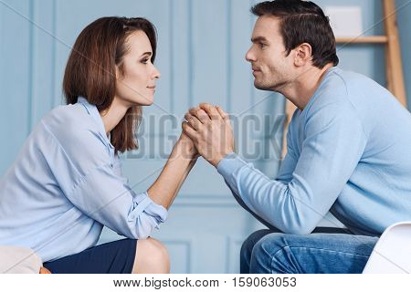 Just believe me. Pleasant lovign positive couple sitting together and holding hands while lookign at each other