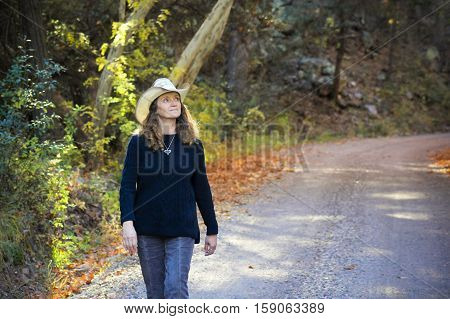 A Portrait of a A Cowgirl Walking a Forest Road in the Fall