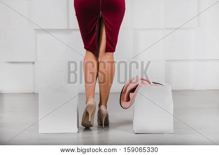 Beautiful sexy female legs in high heel shoes and shopping bags with copy space against modern white wall back view . Shopping Retail