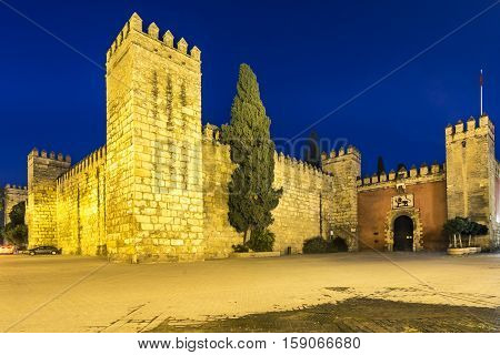 Night view of the Gate and wall to Real Alcazar Gardens in Seville in Andalusia, Spain