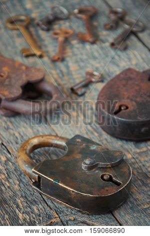 Old padlocks with keys lie on a wooden board