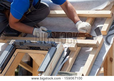 Skylight installation. Roofer builder worker use saw to cut a wooden beam poster