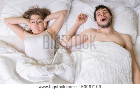 Snoring Concept. Young Woman Is Covering Her Ears. Man Is Snorin