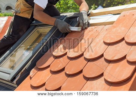 Natural roof tile instaalation. Roofer builder worker use ruller to measure the distance between the tiles. Roof with mansard windows.