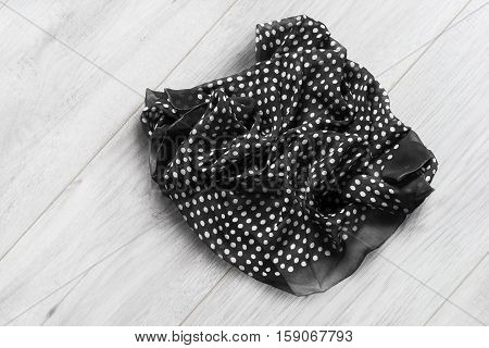 Crumpled silk kerchief closeup on wooden background