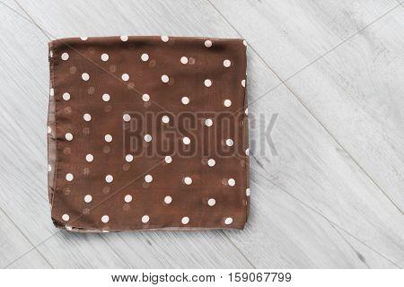 Folded brown silk kerchief on wooden background