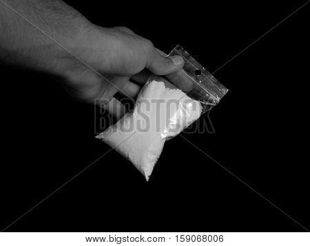 Drug dealer holding bag with cocaine drug powder, men selling drugs junkie on black background in black and white colors