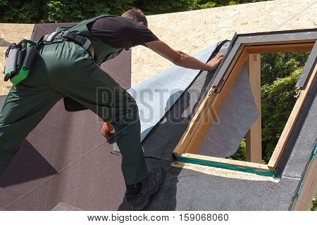 Roofer builder worker installing heating and melting bitumen roofing felt. Skylight. Roof window.