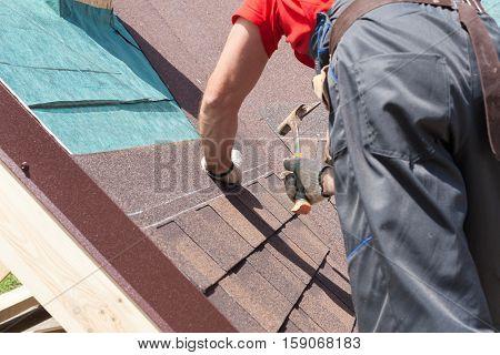 Roofer builder worker use a hammer for installing roofing shingles