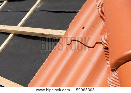 New roof under construction with wooden beams waterproofing layer for corner and natural tile
