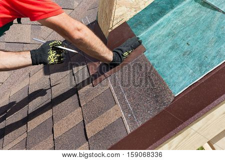 Natural roof tile instaalation. Roofer builder worker marks the distance between the seams