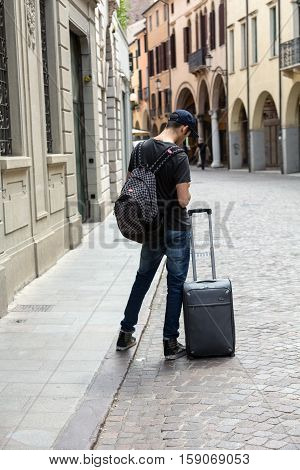 PADUA, ITALY - MAY 3, 2016: the lost tourist with the suitcase on the street in Padua. Italy