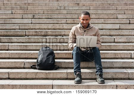 Picture of young african happy man sitting on staircase and using laptop. Looking at laptop.