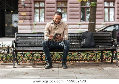 Photo of african happy man with tablet sitting on wooden bench near backpack and typing. Look at tablet.
