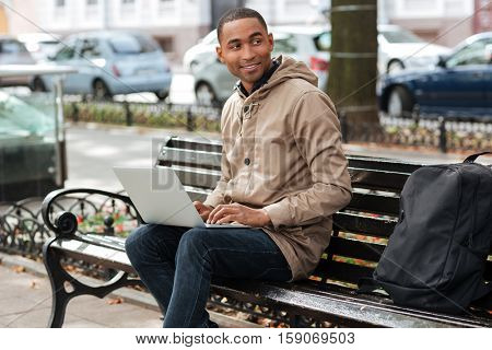 Photo of african happy man with laptop sitting on a wooden bench near backpack and typing. Look aside.