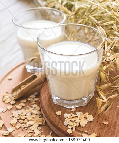 Two Glasses Of Milk And Oat Spikelets On Rustic Table